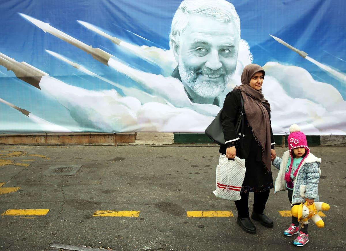 Nainen lapsensa kanssa käveli Quassim Suleimania esittävän julisteen ohi Teheranissa.
