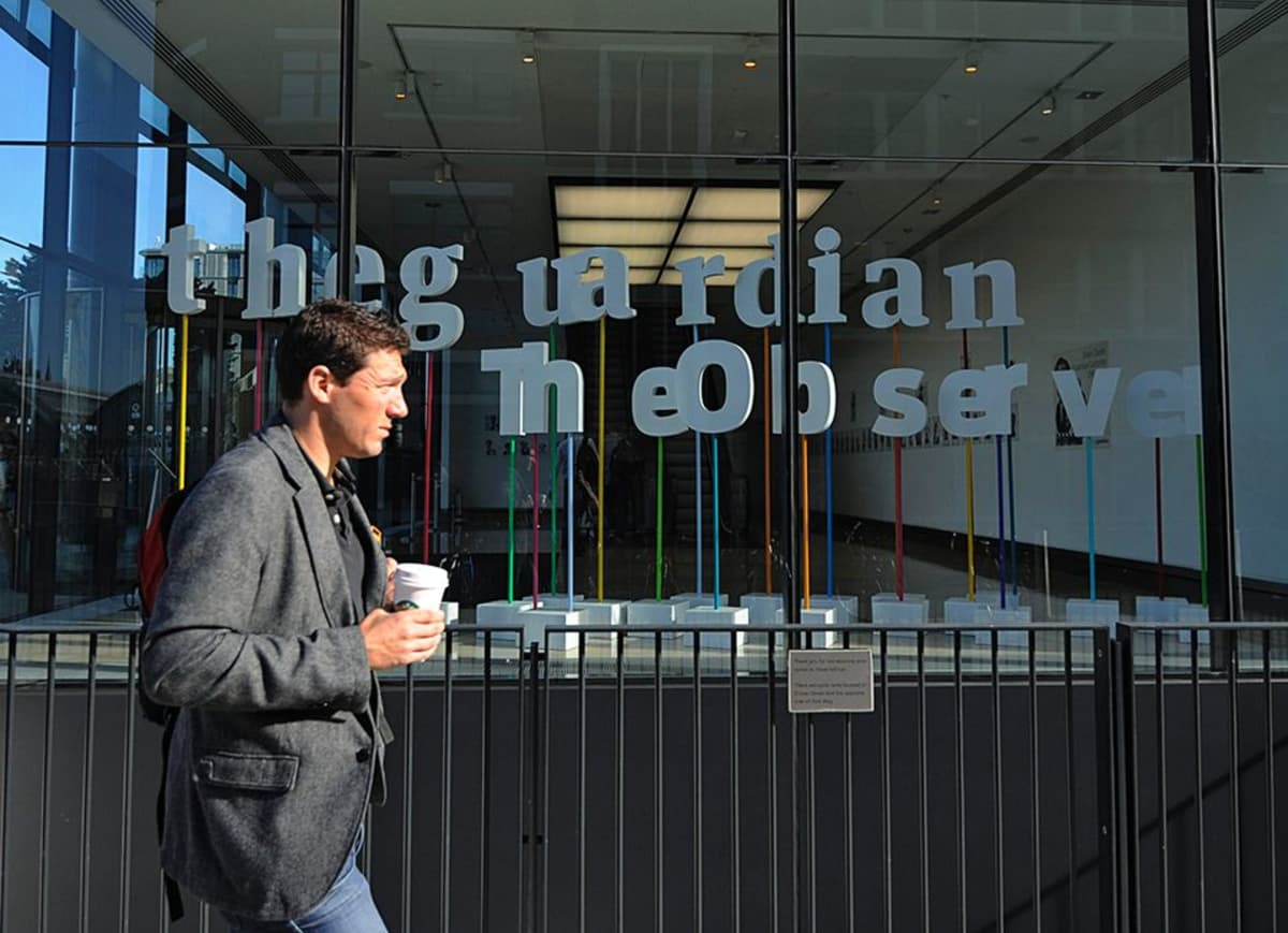 Mies kävelee Starbucksin take away -kahvi kädessään The Guardianin toimistojen ohi Lontoossa.