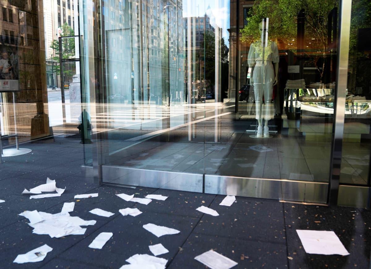 Vaateliikkeen ovet ovat kiinni. Sisällä näkyy muotinukke. Kadulla ovien edessä on papereita hajallaan. Lasiovista heijastuu tyhjä katu.