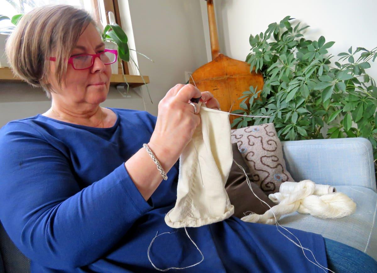 Liisa Kylmänen istuu sohvalla neulomassa silkkisukkaa ohuenohuilla puikoilla,taustalla huonekasveja ja nurkassa sello.