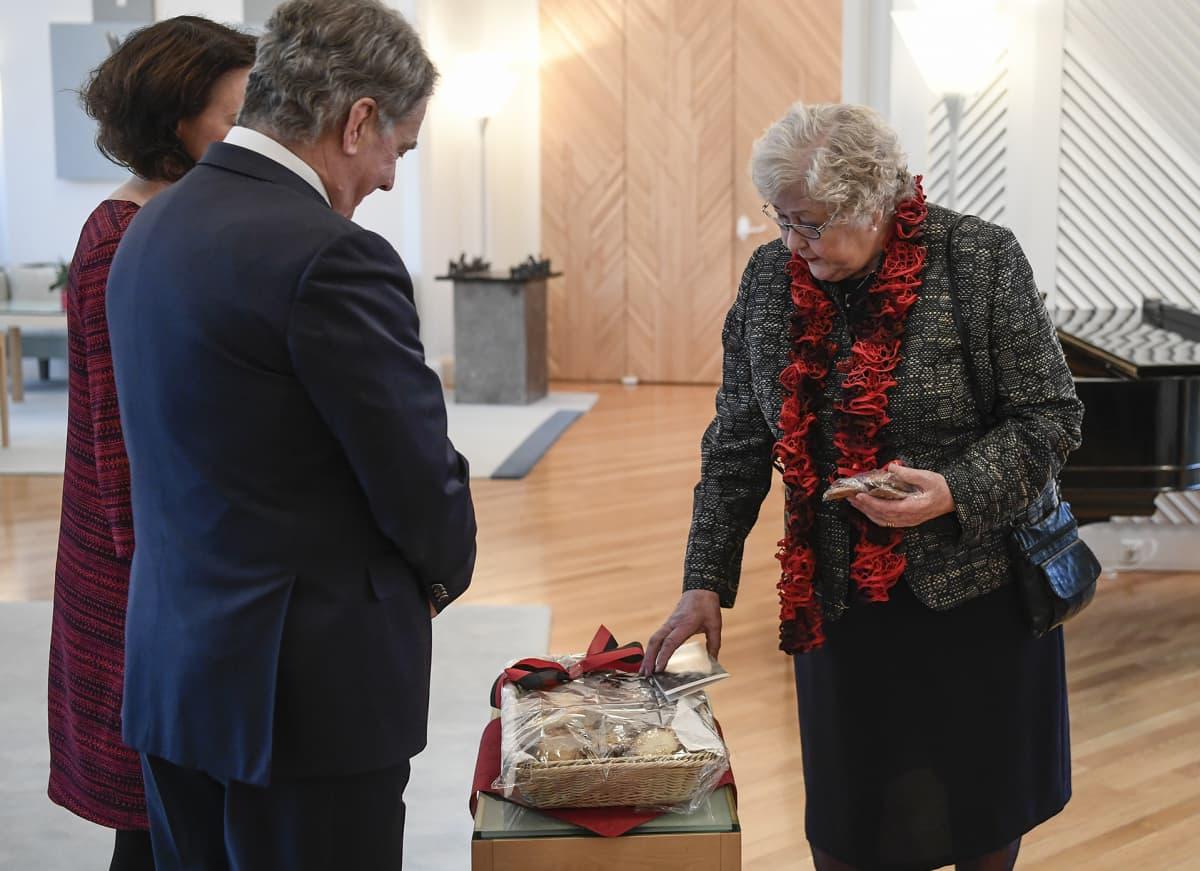 Rouva lahjoittaa karjalanpiirakoita presidenttiparille.