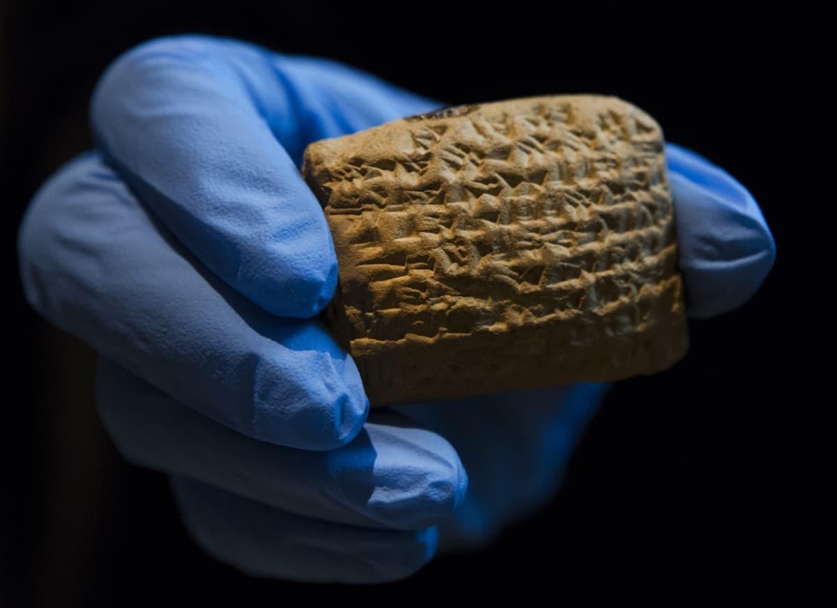 Pieni savitaulu, joka on täynnä nuolenpääkirjoitusta, museotyöntekijän hansikoidussa kädessä.