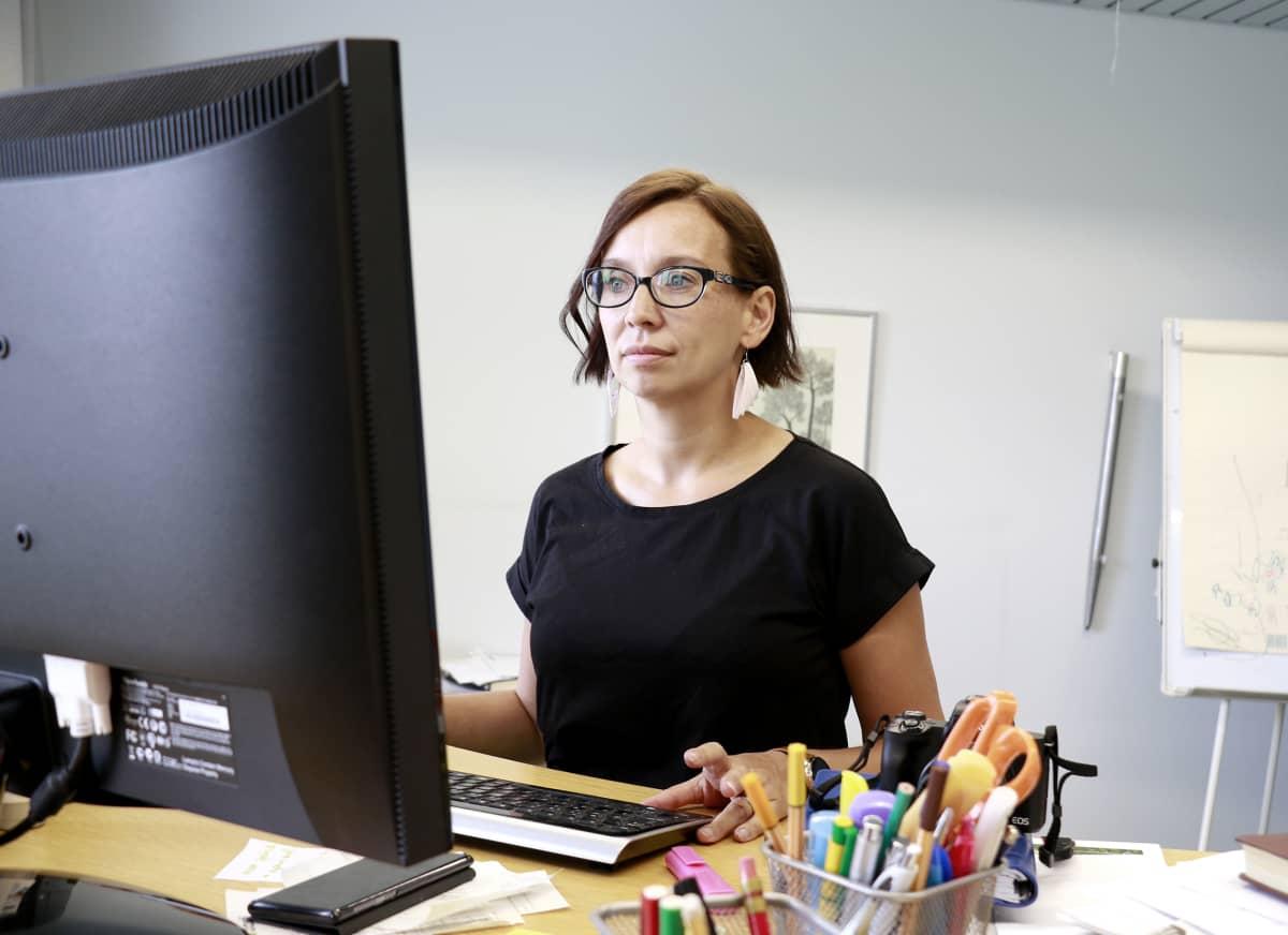 Päätoimittaja Heli Keskinen työskentelee tietokoneella.