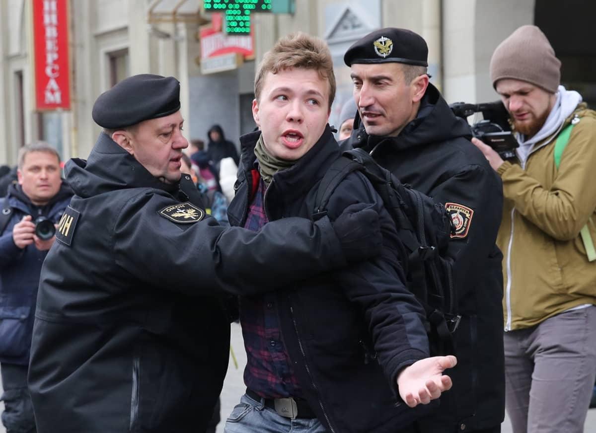 Protasevitš kahden poliisin välissä, taustalla ilmeisesti toimittajia kameroiden kanssa.
