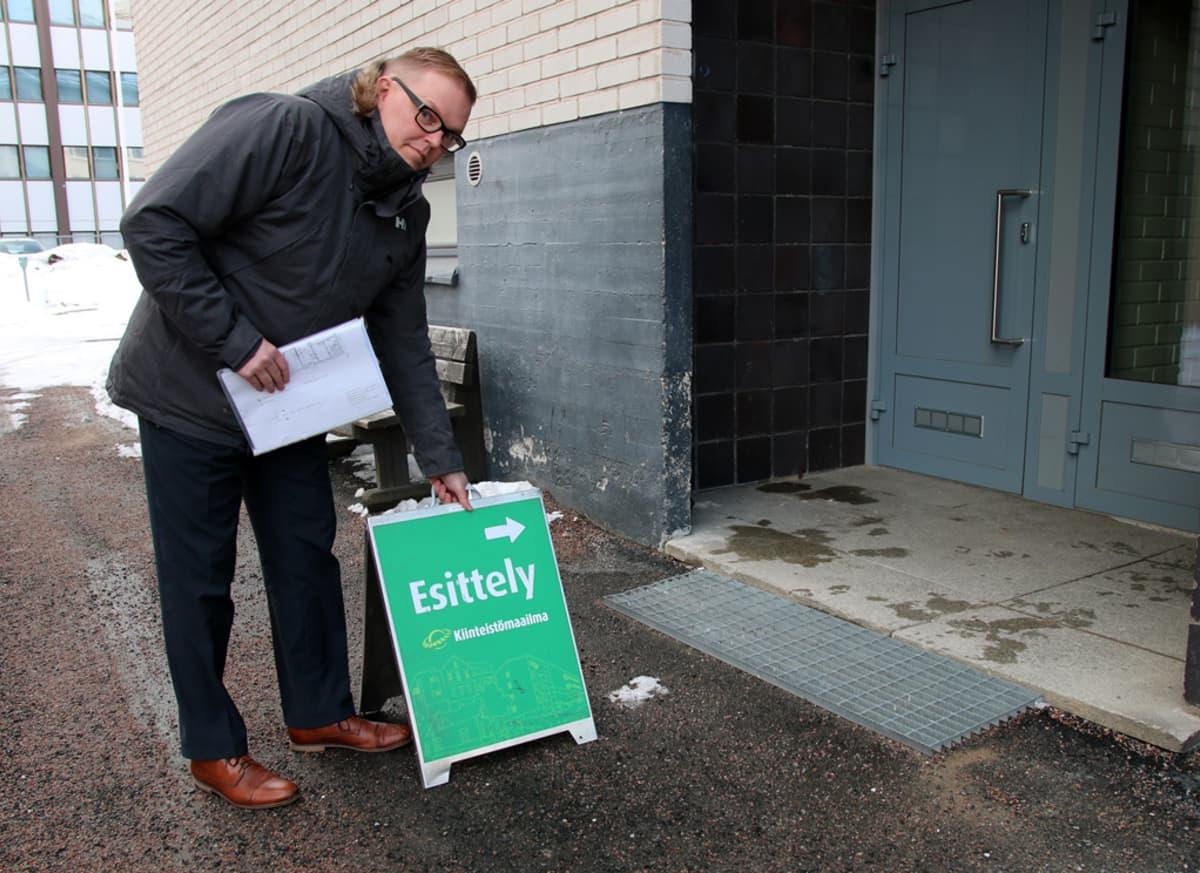 Kiinteistömaailma Rovaniemen toimitusjohtaja Mika Lehtiniemi asettelee vihreää esittelykylttiä talon sisäänkäynnin eteen.