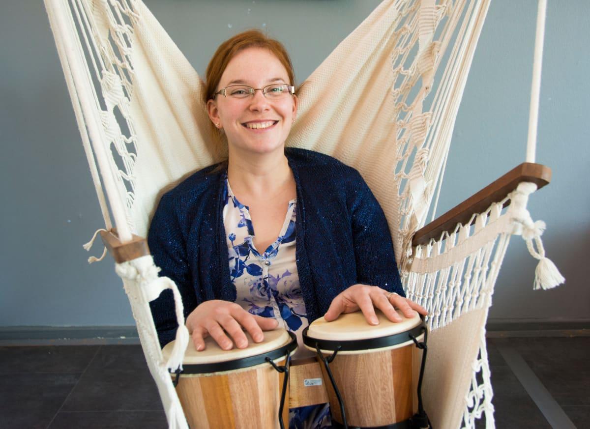 Yhteisömuusikko Miia Kaunisto istuu riippukeinussa ja pitelee sylissään rumpuja.