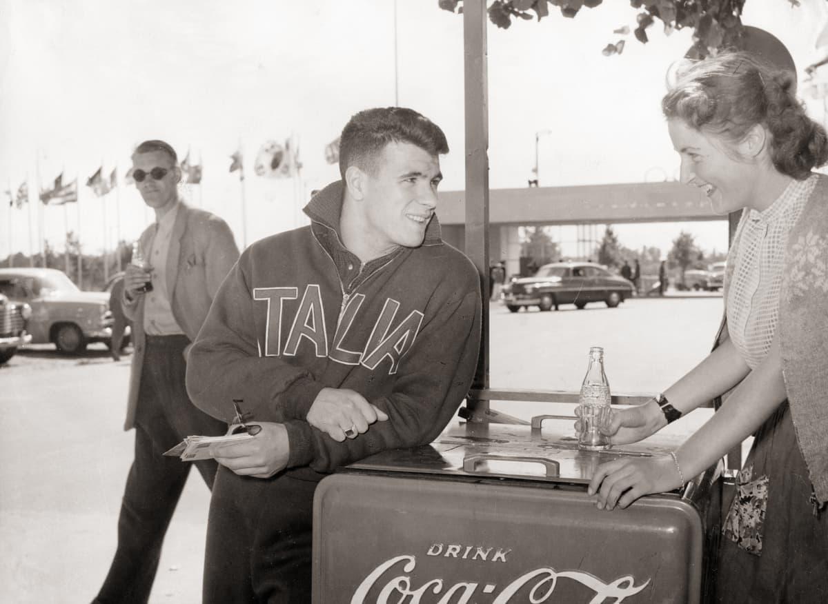 Italian joukkueen urheilija ostaa Coca-colaa myyjättäreltä.