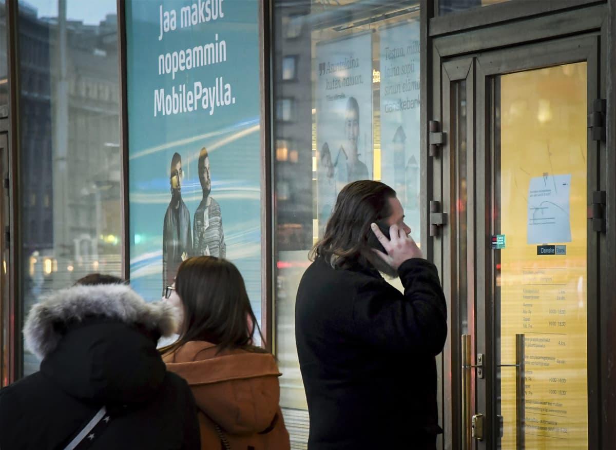Mies puhuu puhelimeen suljetun pankin oven takana