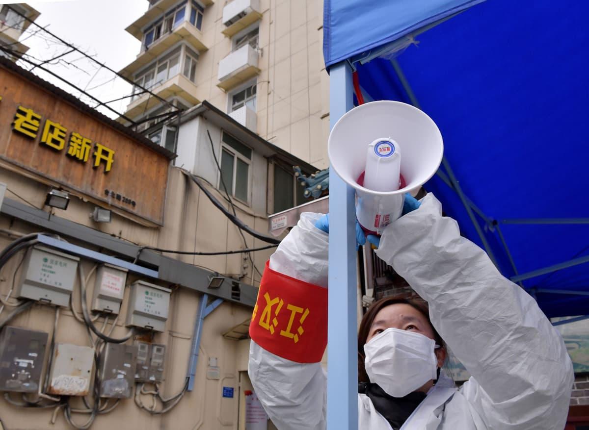 Wuhanin hallinnon työntekijä asentaa megafonia kadulla Wuhanissa 10. helmikuuta 2020.