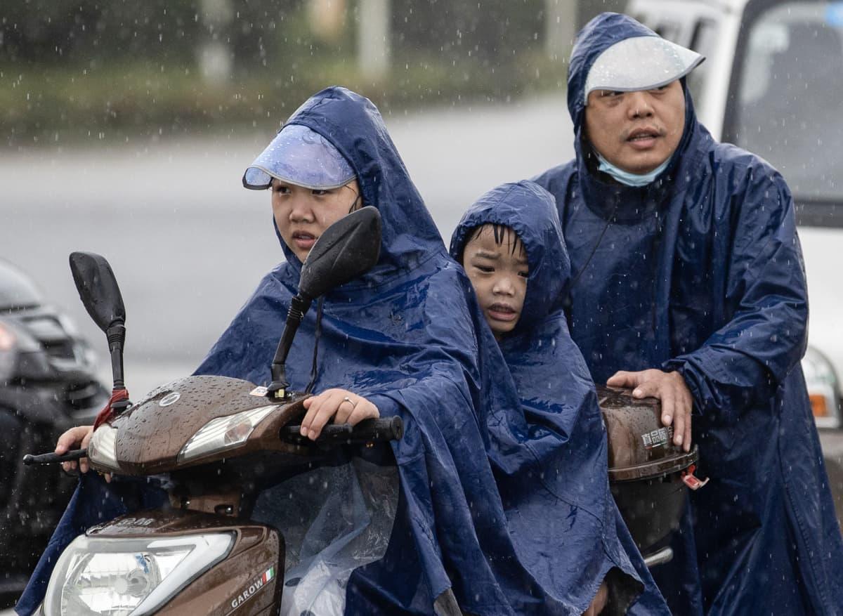 Perhe sadevarusteissa ajaa mopolla.