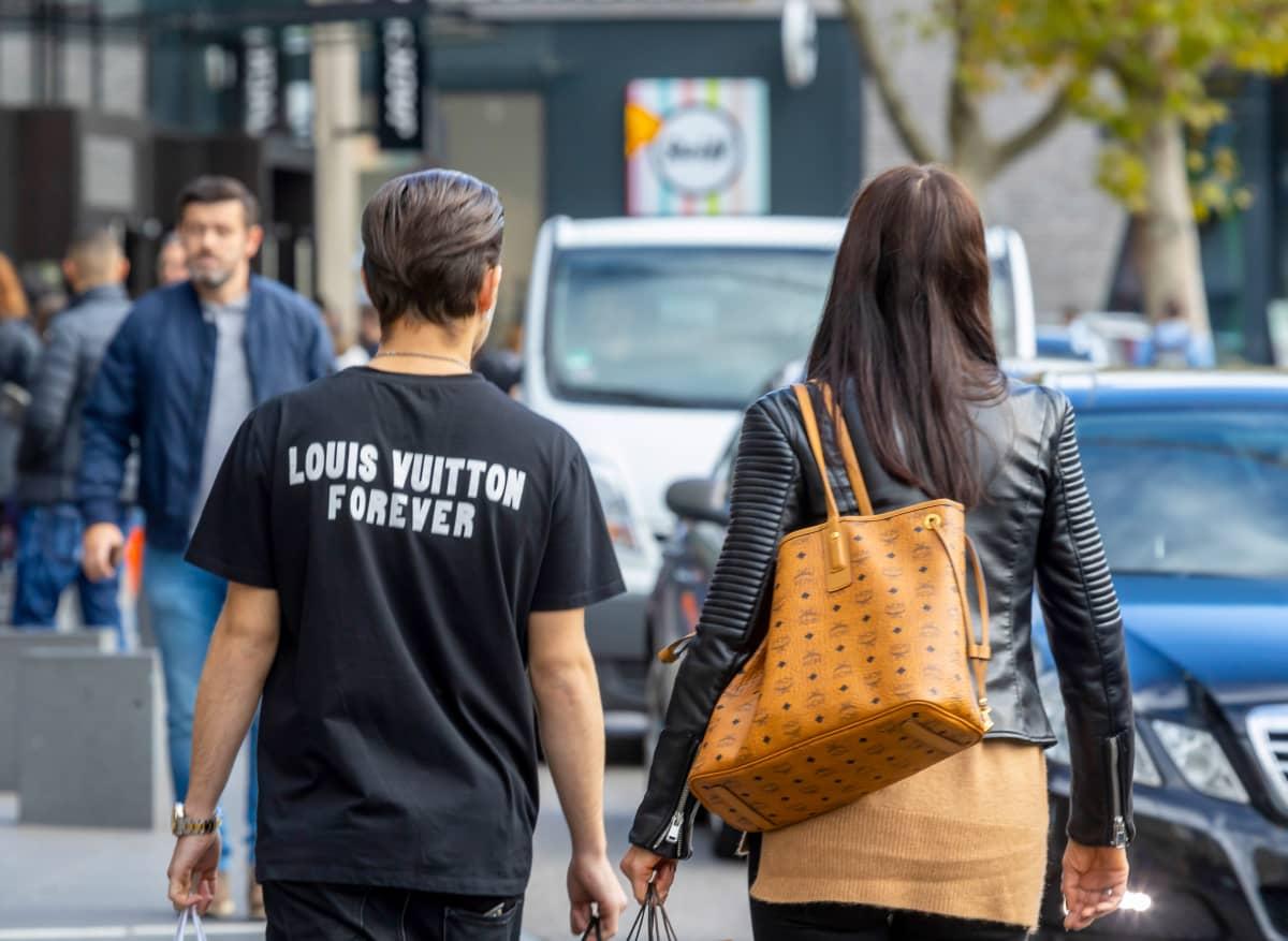 Louis Vuitton -teksti miehen t-paidassa ja naisella Vuittonin laukku.