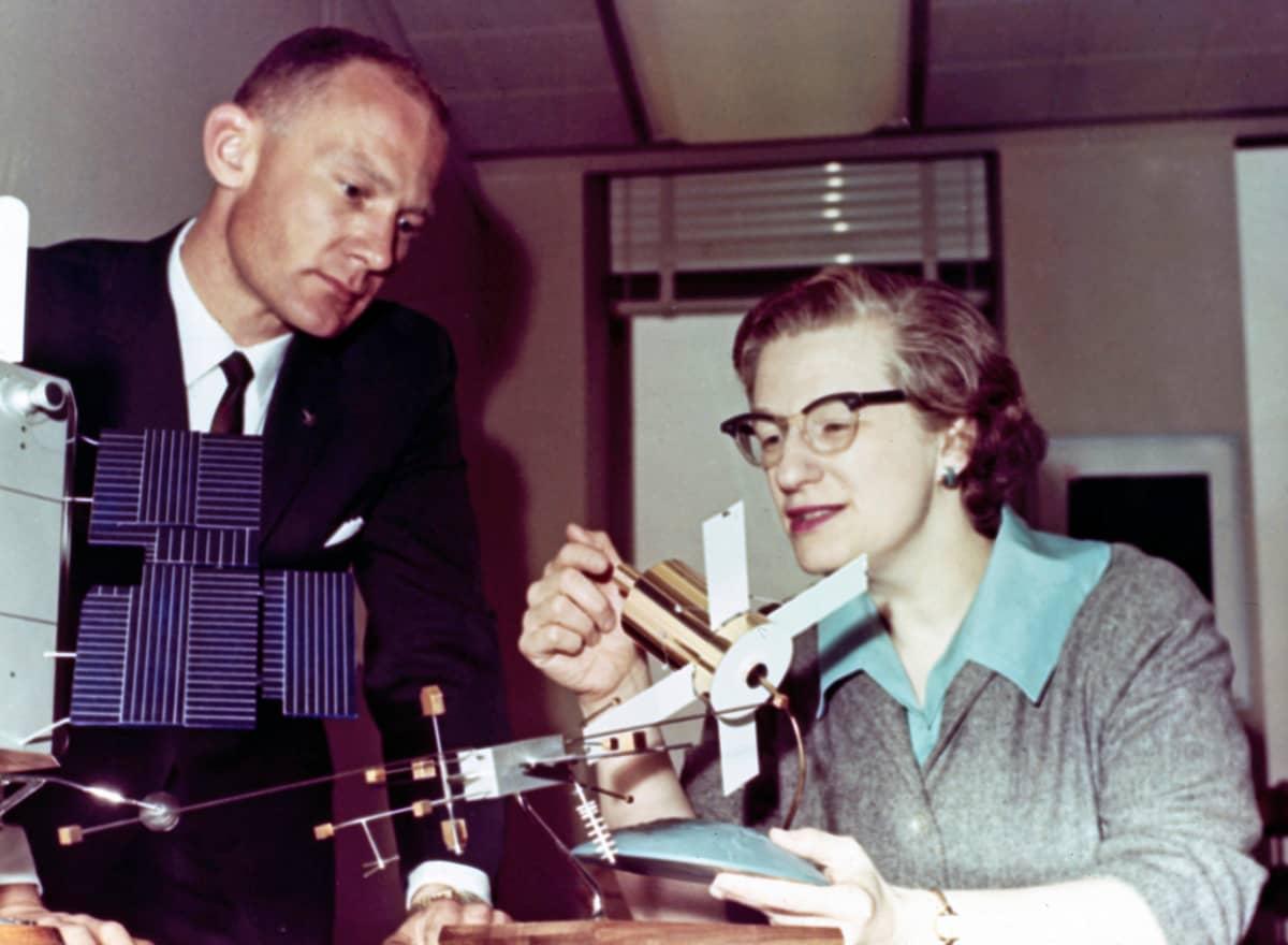 Pöydän ääressä istuvan  naisen kädessä on observatorion pienoismalli. Mies on kumartunut katsomaan sitä.