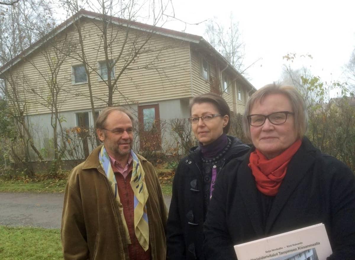 Kalle Heiska, Kirsi Kaivanto ja Seija Hirvikallio kaksikerroksisen rivitalon edessä