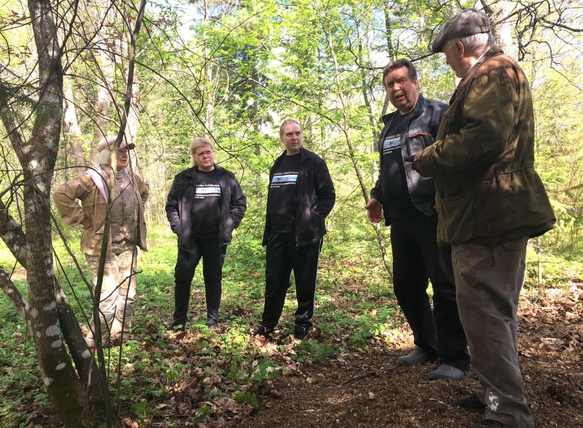 ihmisiä pihalla metsän reunassa, neuvottelua siilien pesälaatikoiden sijoittelusta