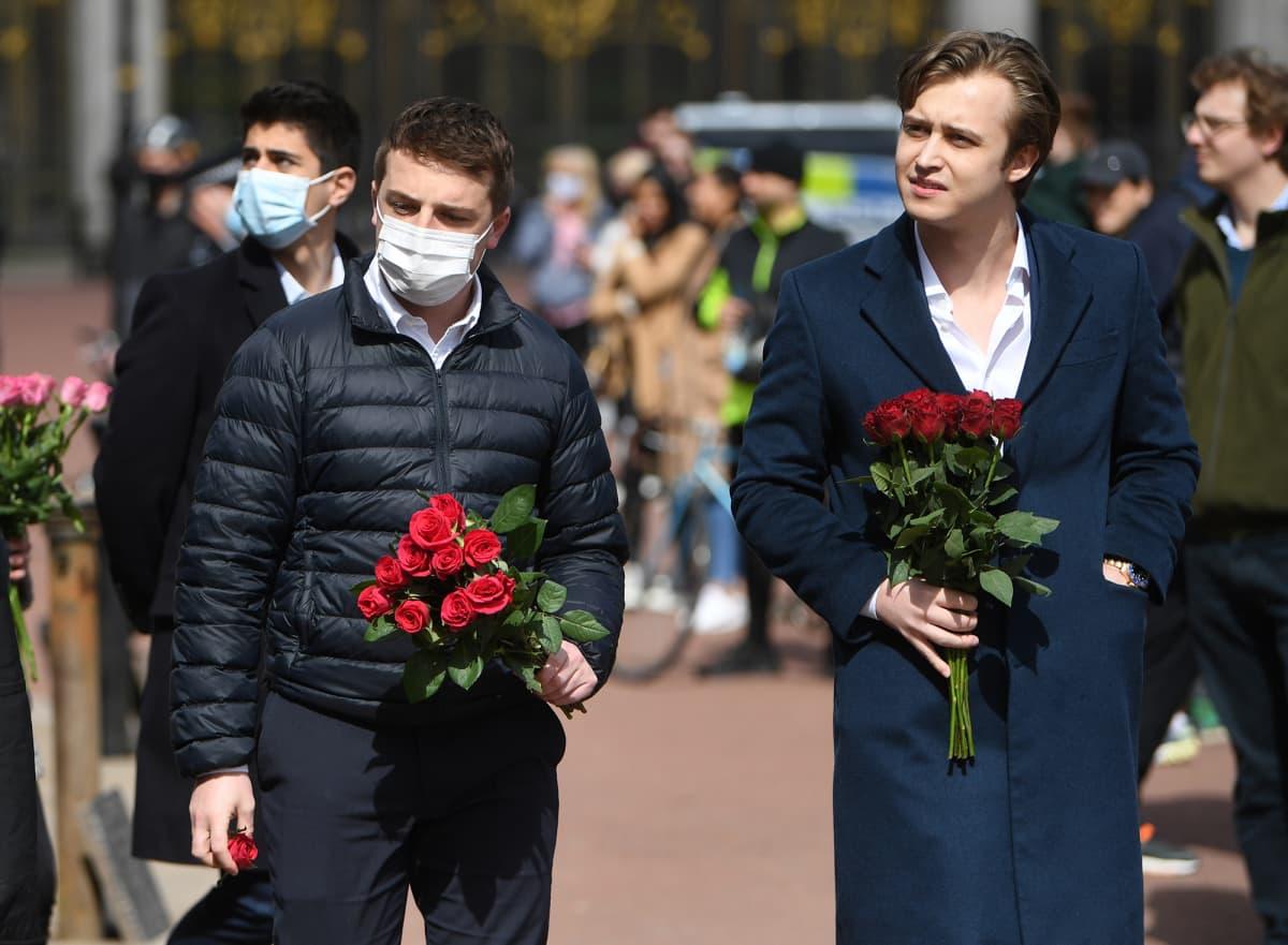 Ihmiset tuovat kukkia Buckinghamin palatsin edustalle.