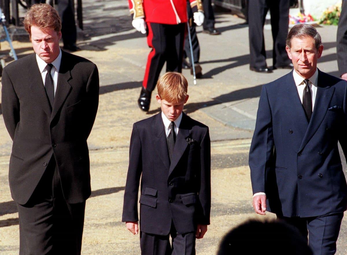 Harry kävelee miesten keskellä. Kaikki ovat pukeutuneet mustiin.