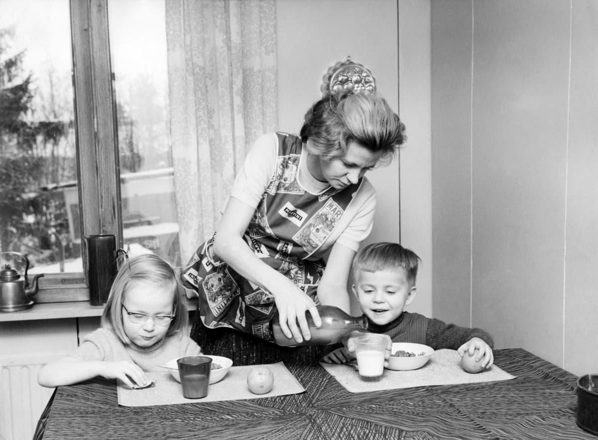 Kotiäiti ja lapset ruokailemassa pöydän ääressä.