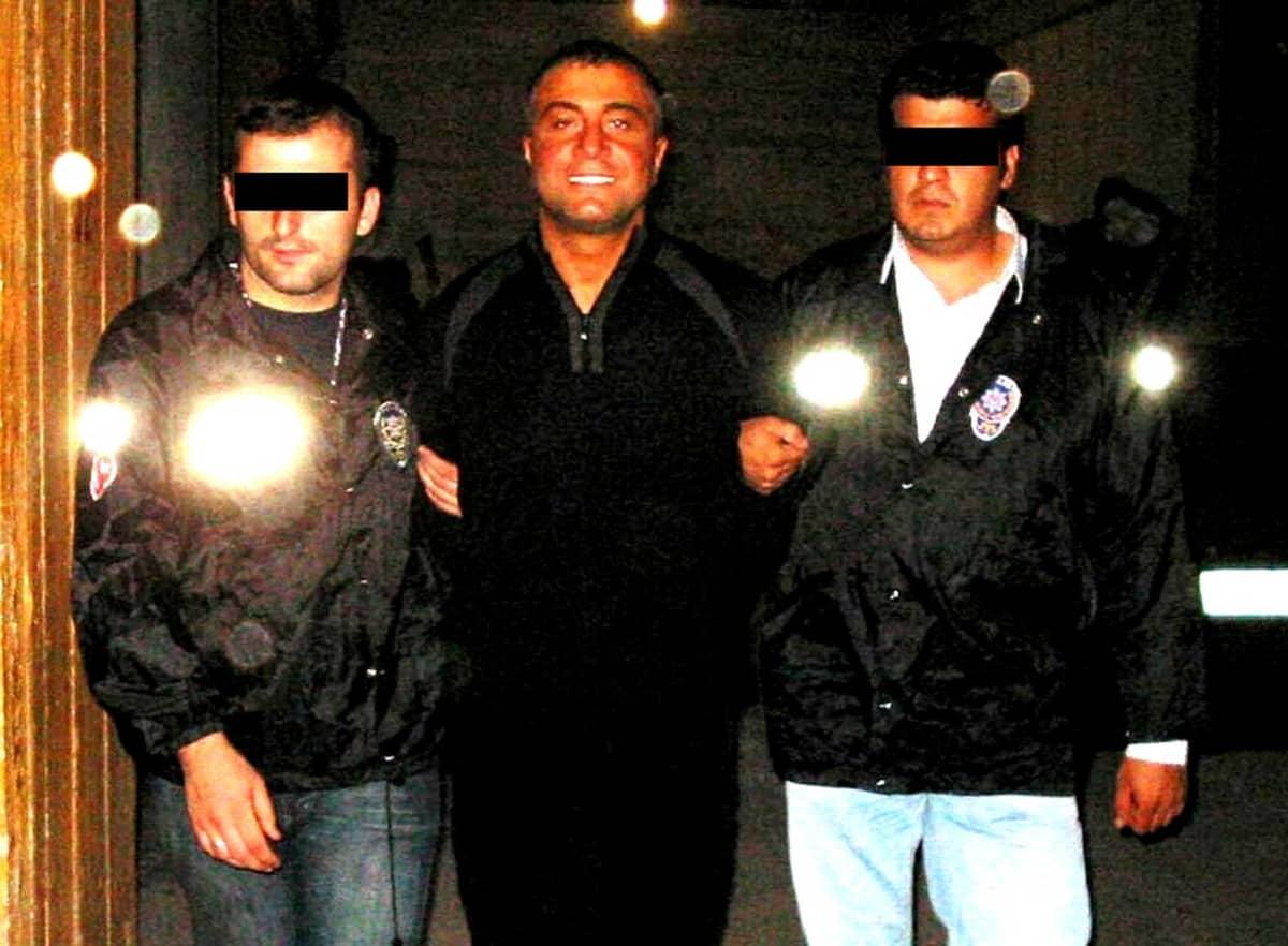 Poliisit pidättävät hymyilevät miehen.