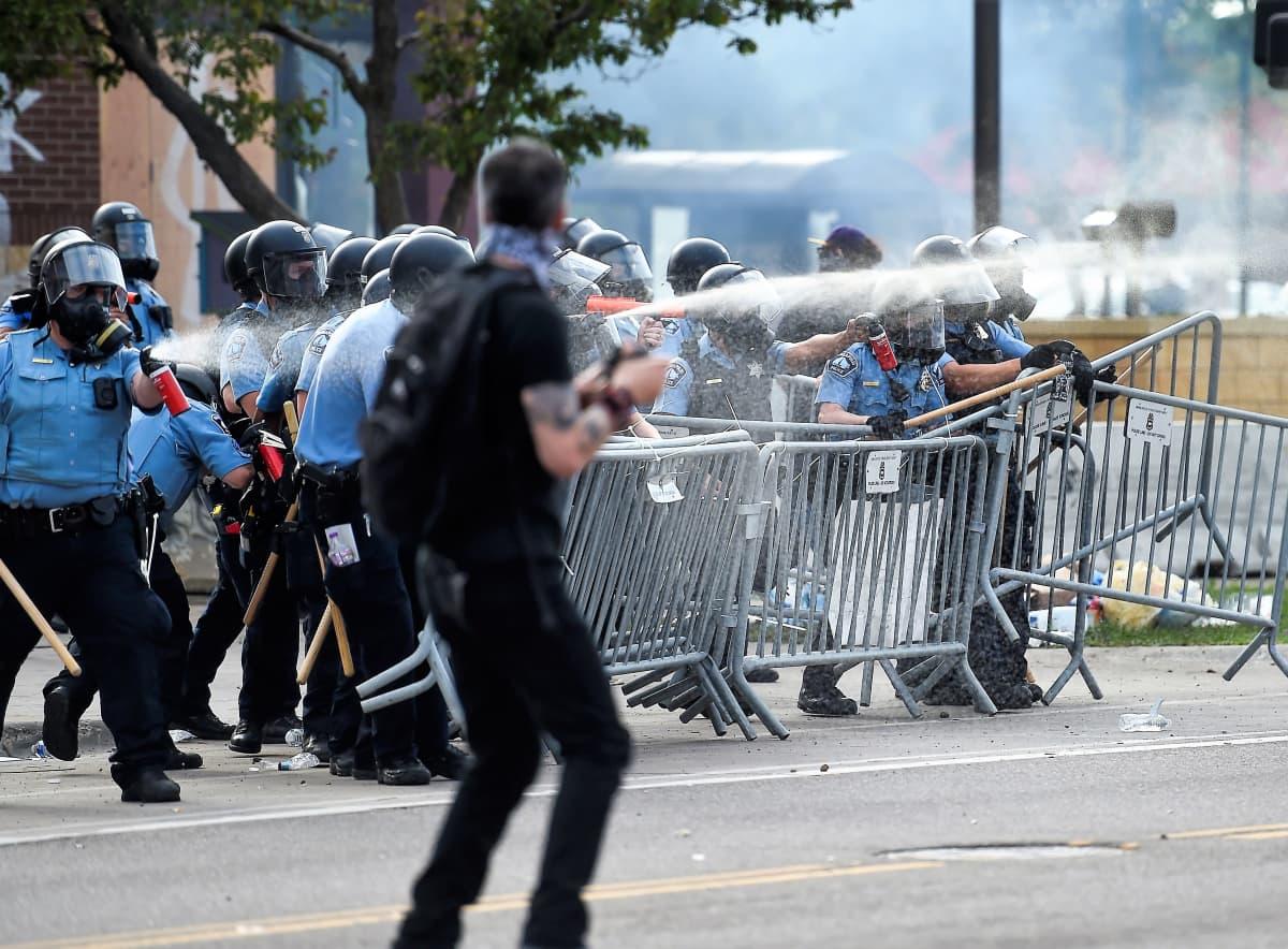oukko mellakkapoliiseja on metalliaidan takana ja suihkuttaa kyynelkaasua. Mielenosoittaja seisoo etualalla.