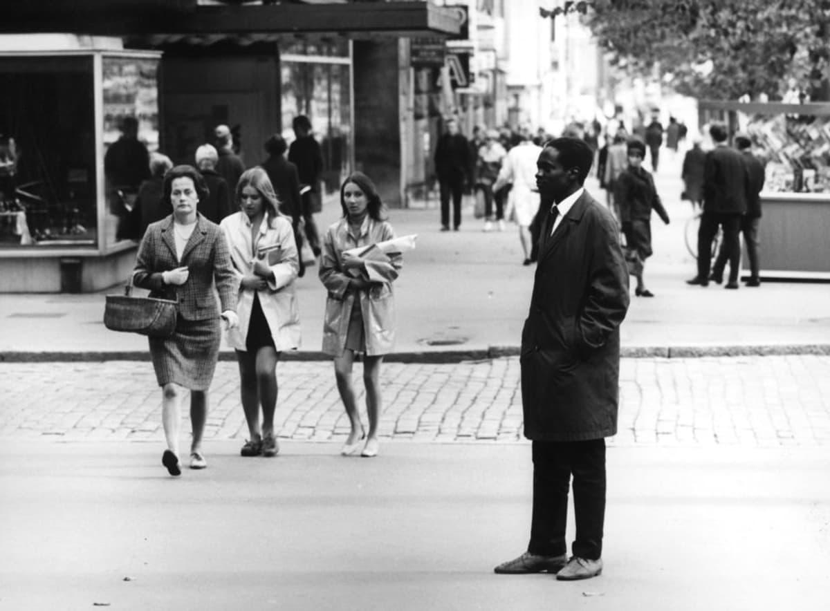 Tummaihoinen mies seisoo Tampereen kadulla. Naisia kävelee vieressä.