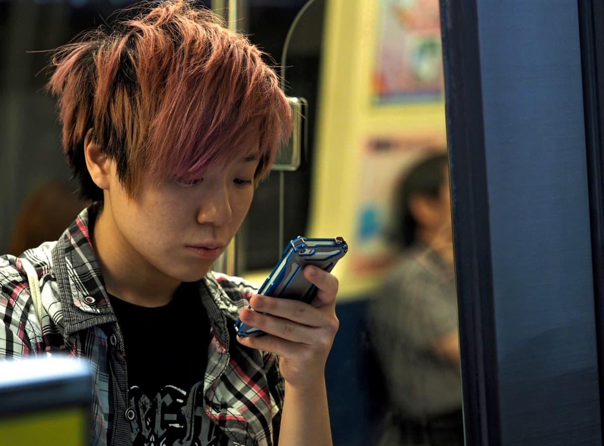 Nuorukainen katselee matkapuhelintaan maanalaisessa.