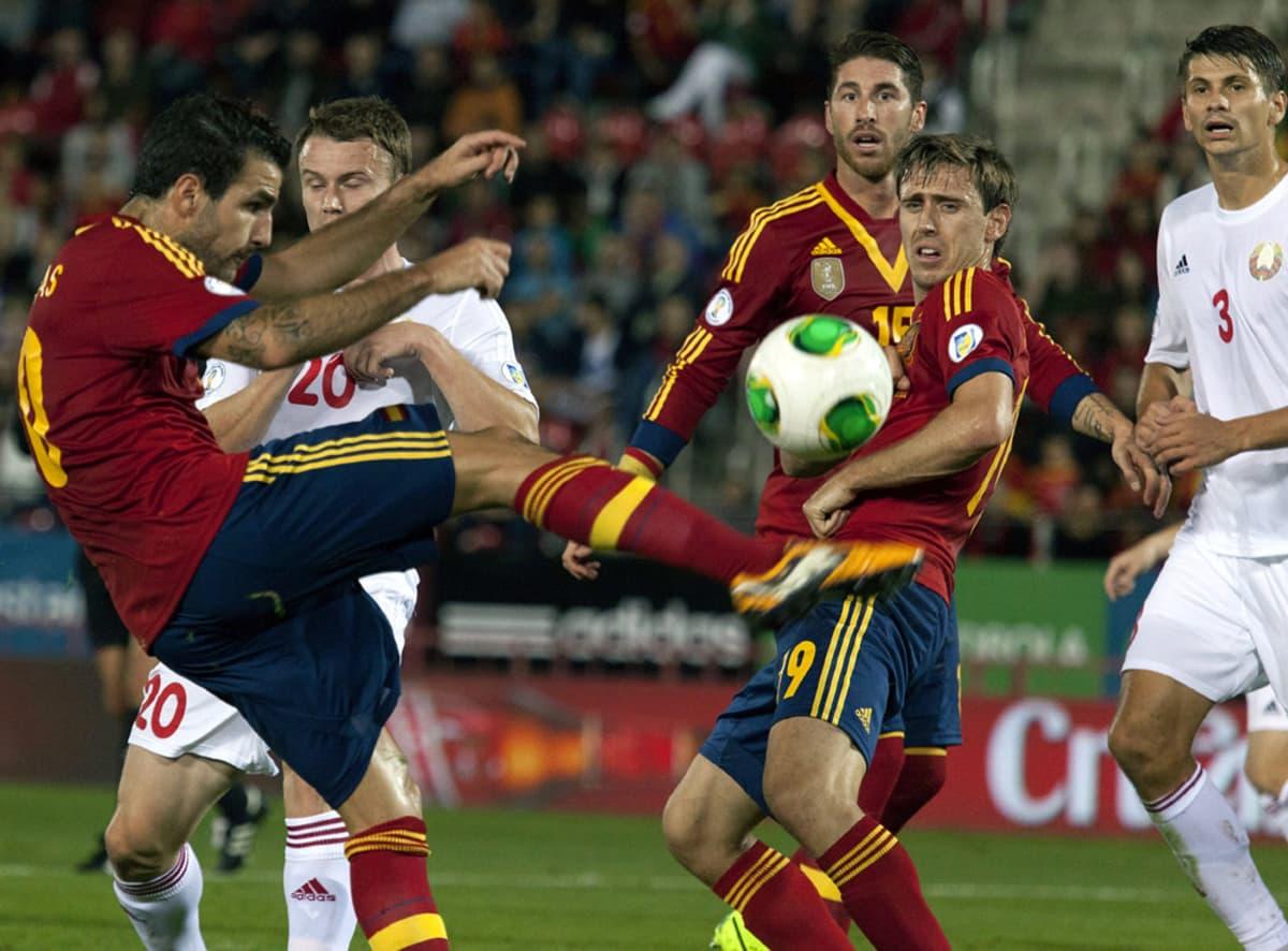 Espanjan Cesc Fabrègas (vas.) pallon kanssa pelaajaryhmän edessä.