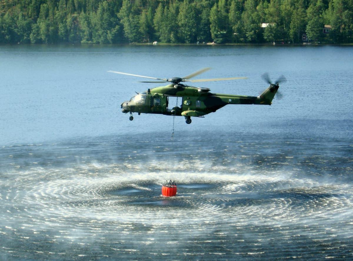 Puolustusvoimien NH90 -kopteri täyttämässä vesisäiliötä.