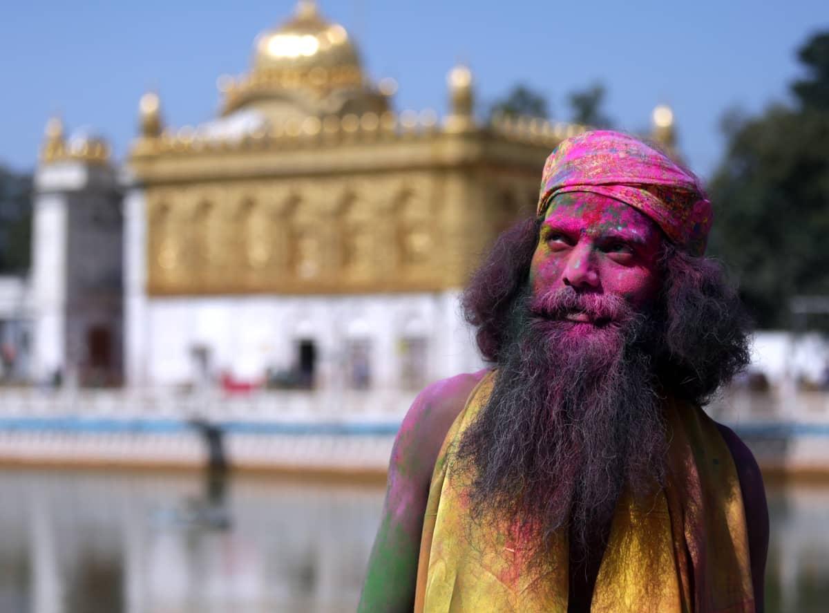 Turbaanipäinen pitkätukkainen mies seisoo temppelin pihalla. Hänet on värjättyeri väreillä.