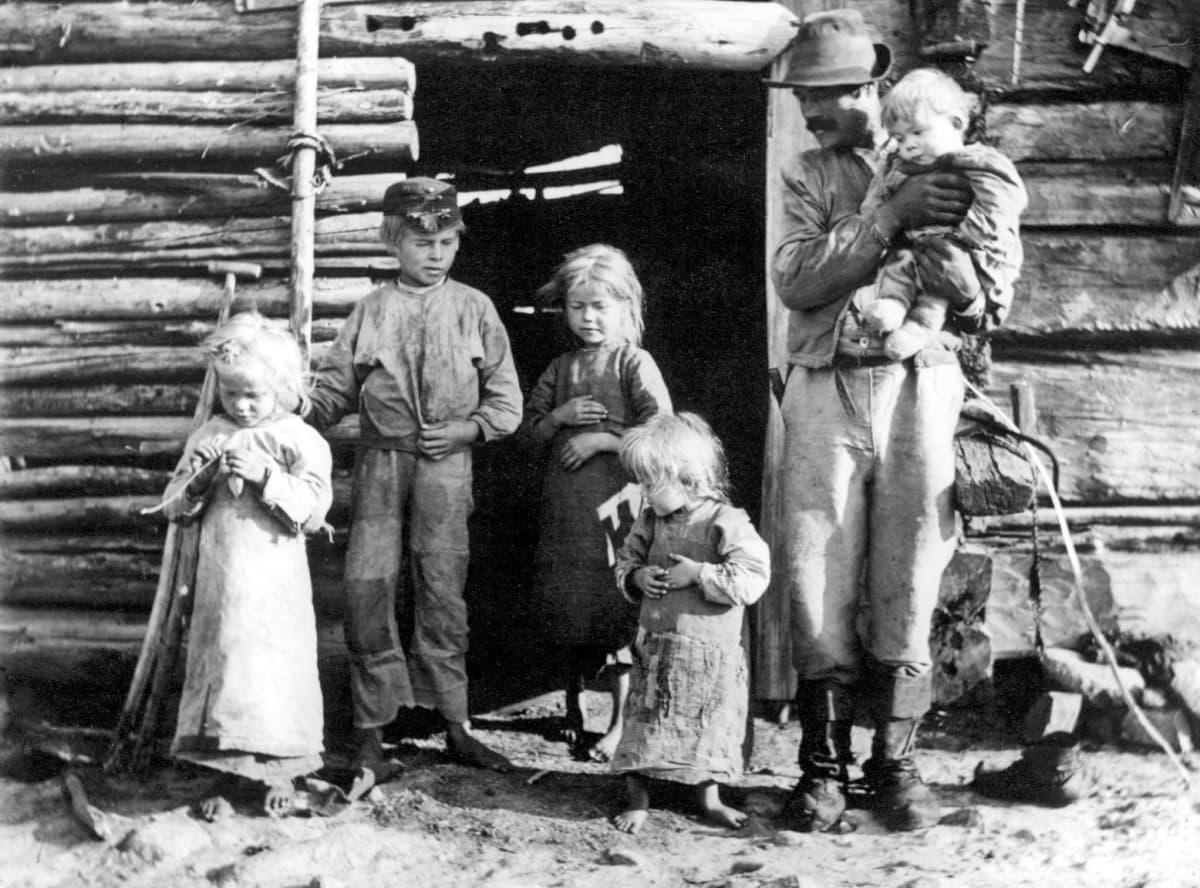 Luukkosen pettua syövä perhe hirsitalon ovella.