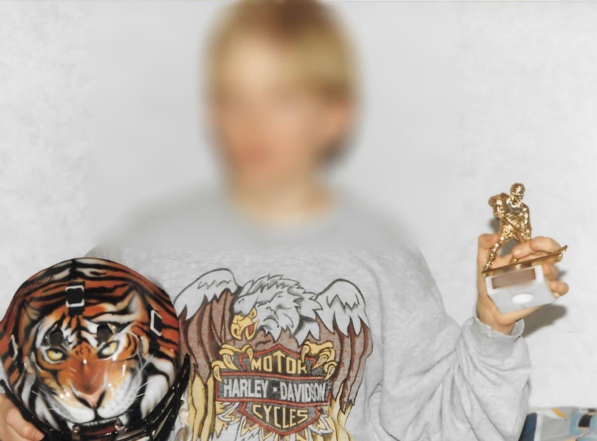 Kuva nuoresta pojasta, joka pitää kädessään jääkiekkoilijapatsasta ja jääkiekkomaalivahdin kypärää, jossa on tiikerinkasvot kuviointina. Pojan kasvot on sumennettu anonyymiteetin vuoksi.
