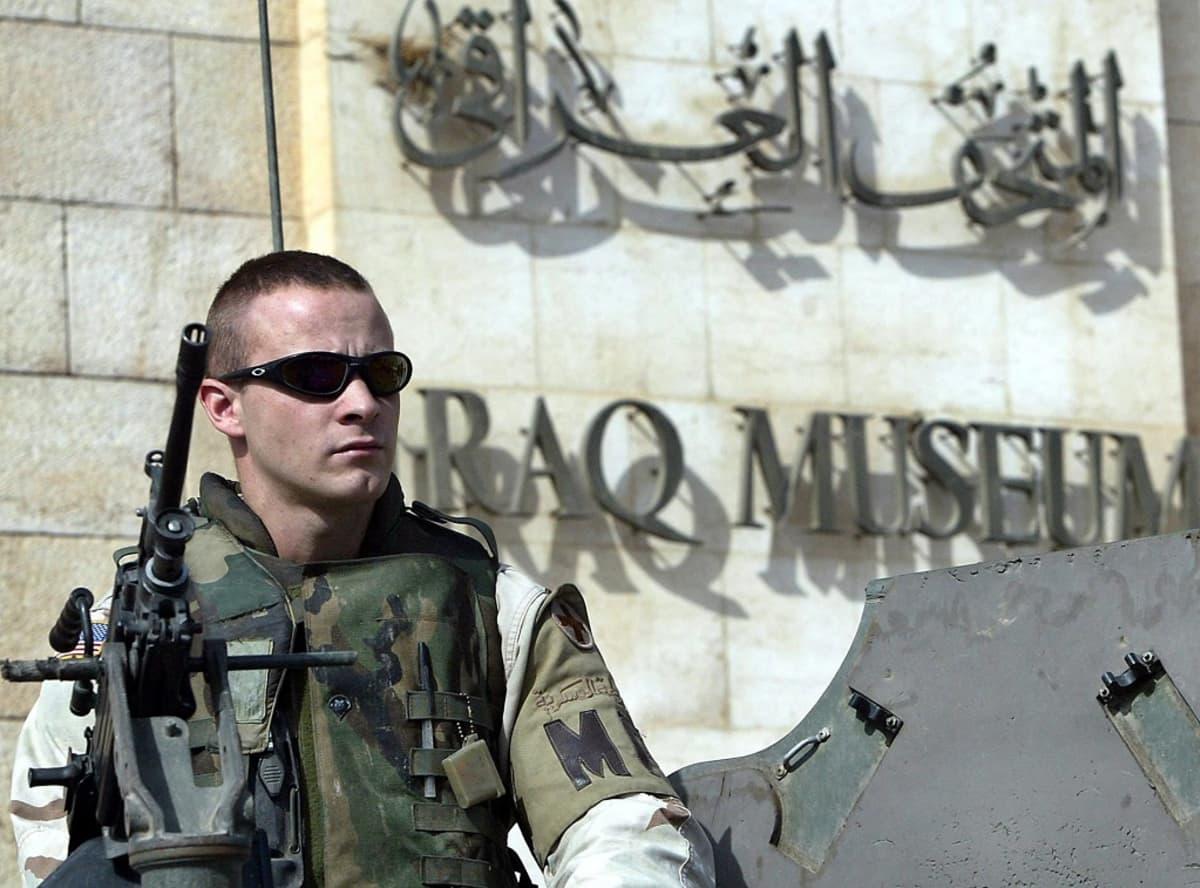 """Amerikkalaissotilas seisoo seinän vieressä maastopuvussa ja luotiliiveissä, silmillään mustat lasit ja edessään konetuliase. Seinässä on arabiankielistä tekstiä ja englanniksi sen alla lukee """"Iraq Museum""""."""