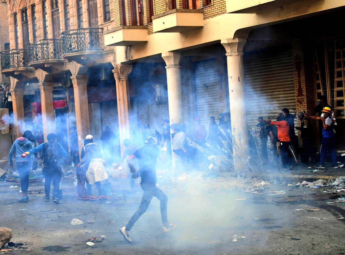 Mielenosoittajat pakenivat poliisin kyynelkaasua Al-Rasheed -kadulla Bagdadissa, Irakissa 23. marraskuuta.