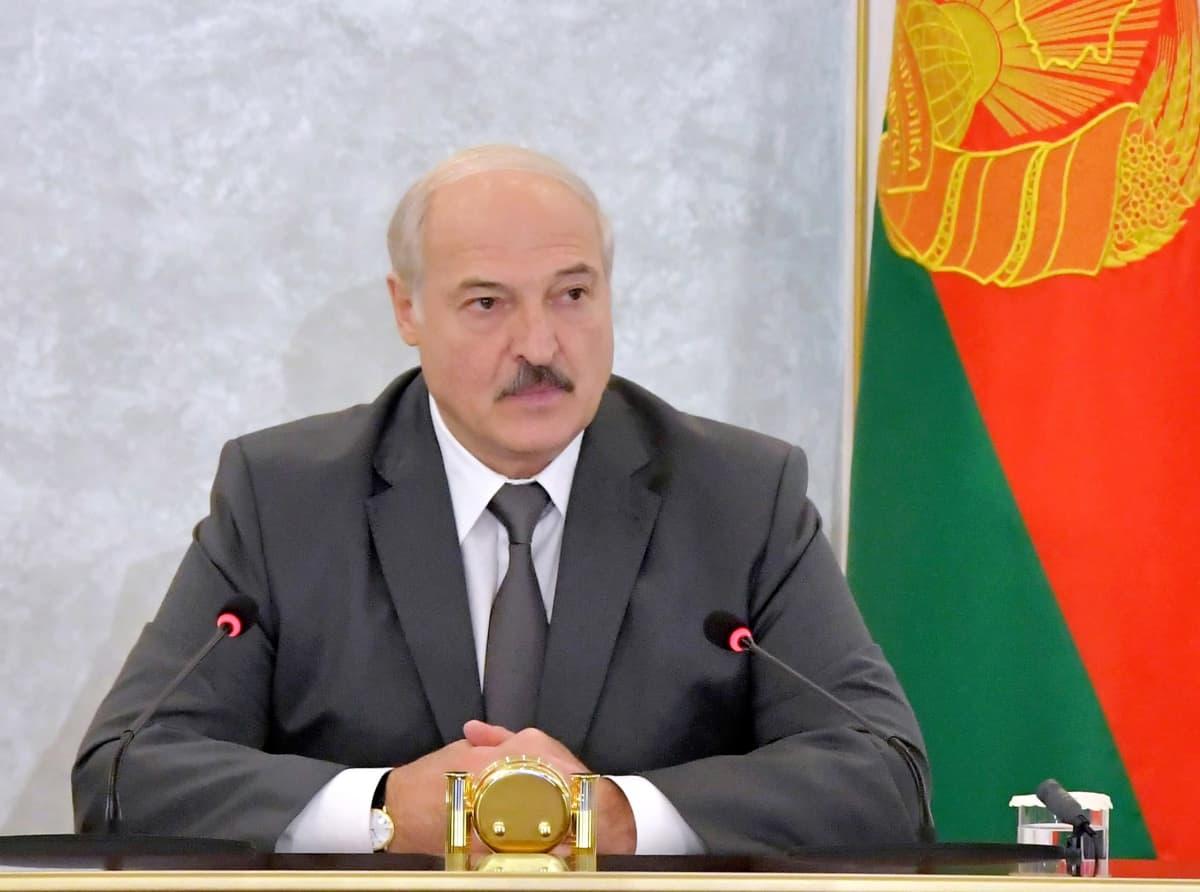 Lukashenka istuu pöydän takana tummanharmaassa puvussa ja kravatissa, Hänen edessään on mikrofoni. Hän on ristinyt kätensä eteensä, Taustalla näkyy Valko-Venäjän punavihreä lippu.