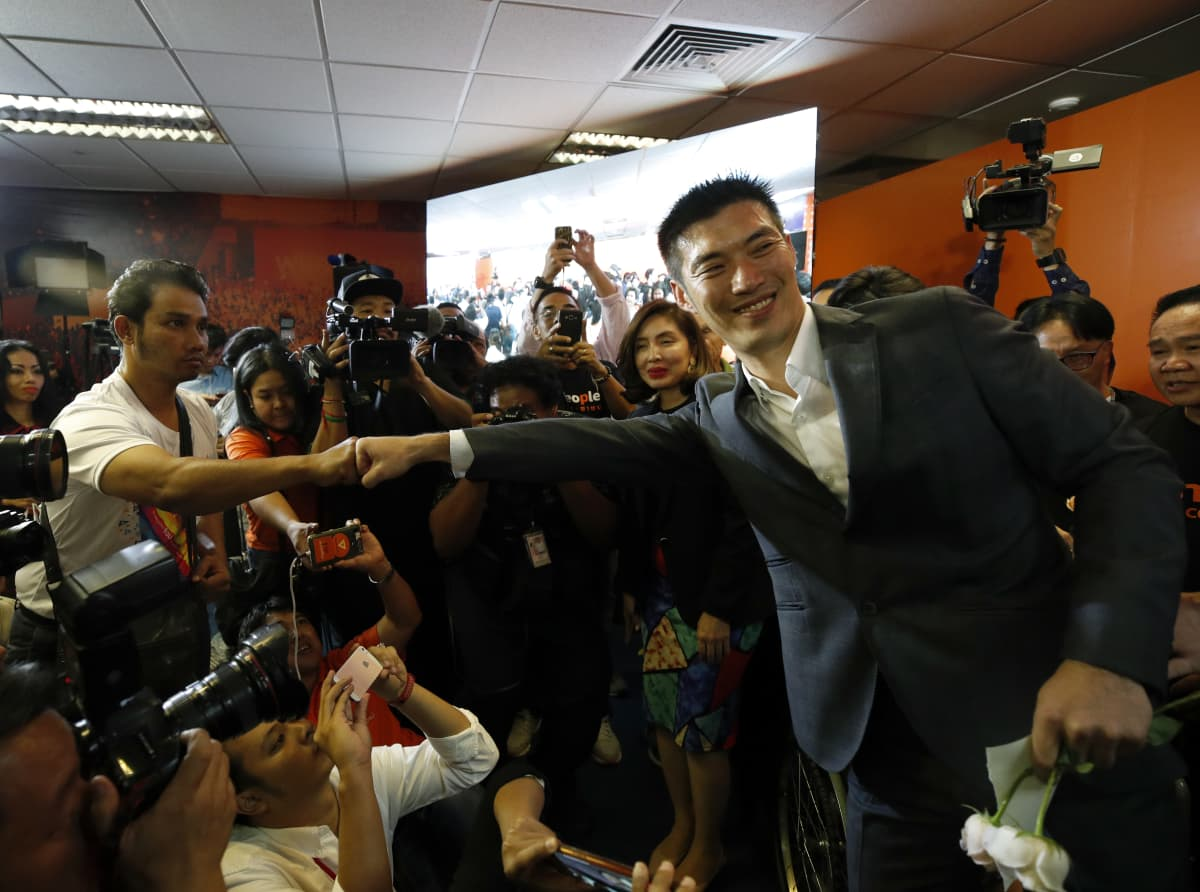 FF-puolueen johtaja tekee nyrkkitervehdyksen toisen miehen kanssa, ympärillä paljon tukijoita kameroineen.