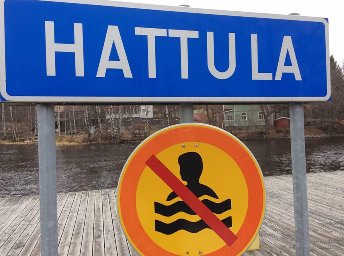 Hattula-kyltti ja uimisen kieltävä liikennemerkki