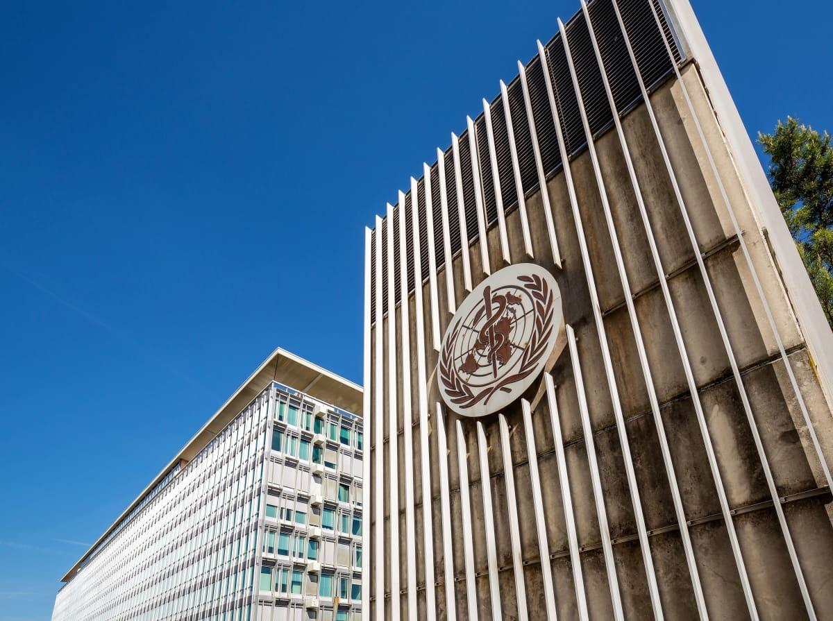 Kuvassa on Maailman terveysjärjestön WHO:n päämaja. Portissa on järjestön logo, jossa on YK:ta kuvaava maapallo ja lehvät ja maapallon keskellä terveydenhuoltoa symboloiva käärme sauvan ympärille kietoutuneena.