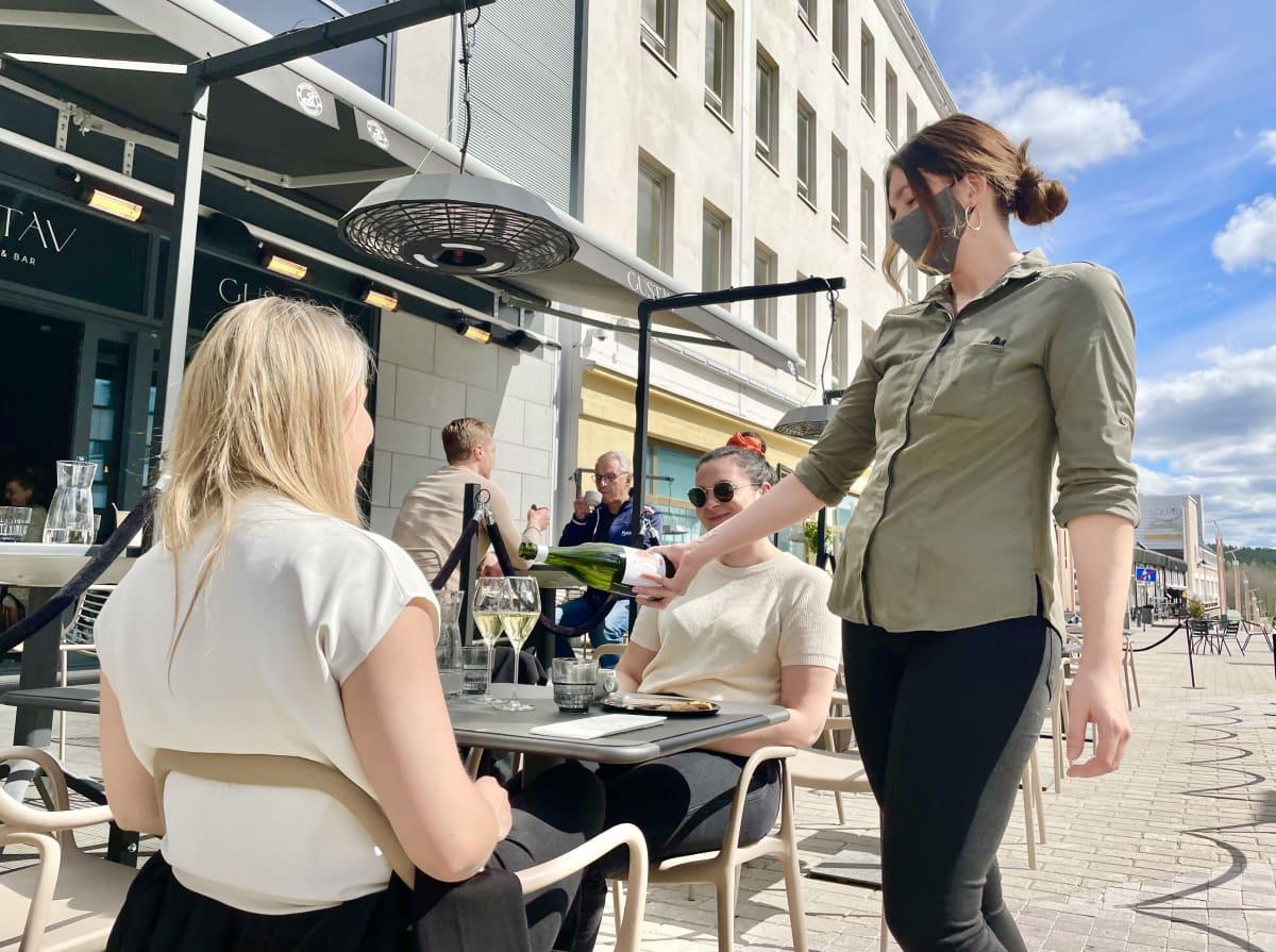 Kaksi naista tilaa ravintolassa valkoviiniä
