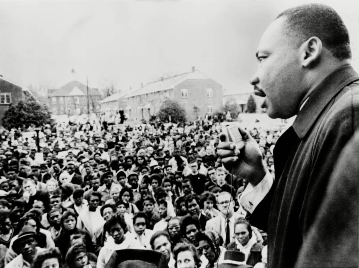 Mustavalkokuvassa oikealla oleva Martin Luther KIng puhuu mielenosoittajille.
