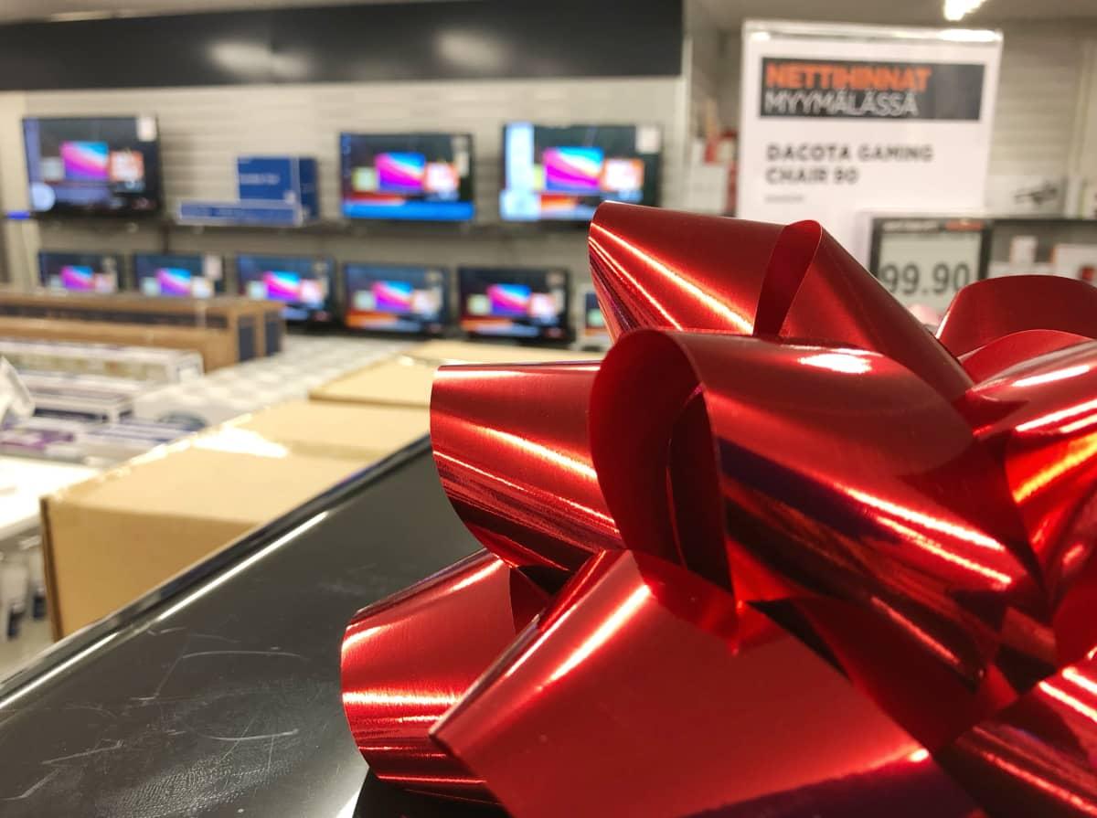 Iso punainen rusetti kuvassa etualalla, taustalla televisioita seinällä kodinkoneliikkeessä.