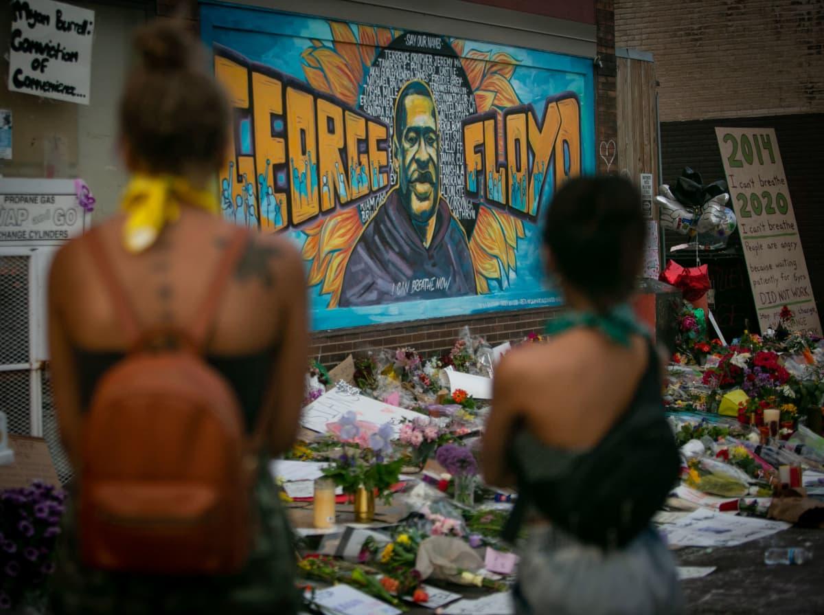 Kukkia ja kortteja kadulla seinämaalauksen edessä