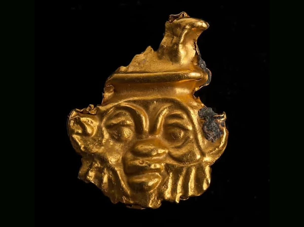 Kultainen amuletti, jossa on partaiset miehenkasvot.