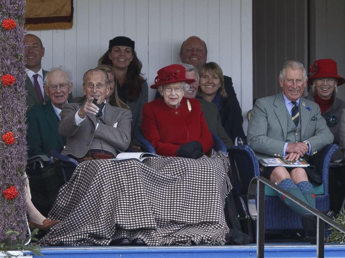 prinssi Philip, kuningatar Elisabet ja prinssi Charles istumassa katsomossa.