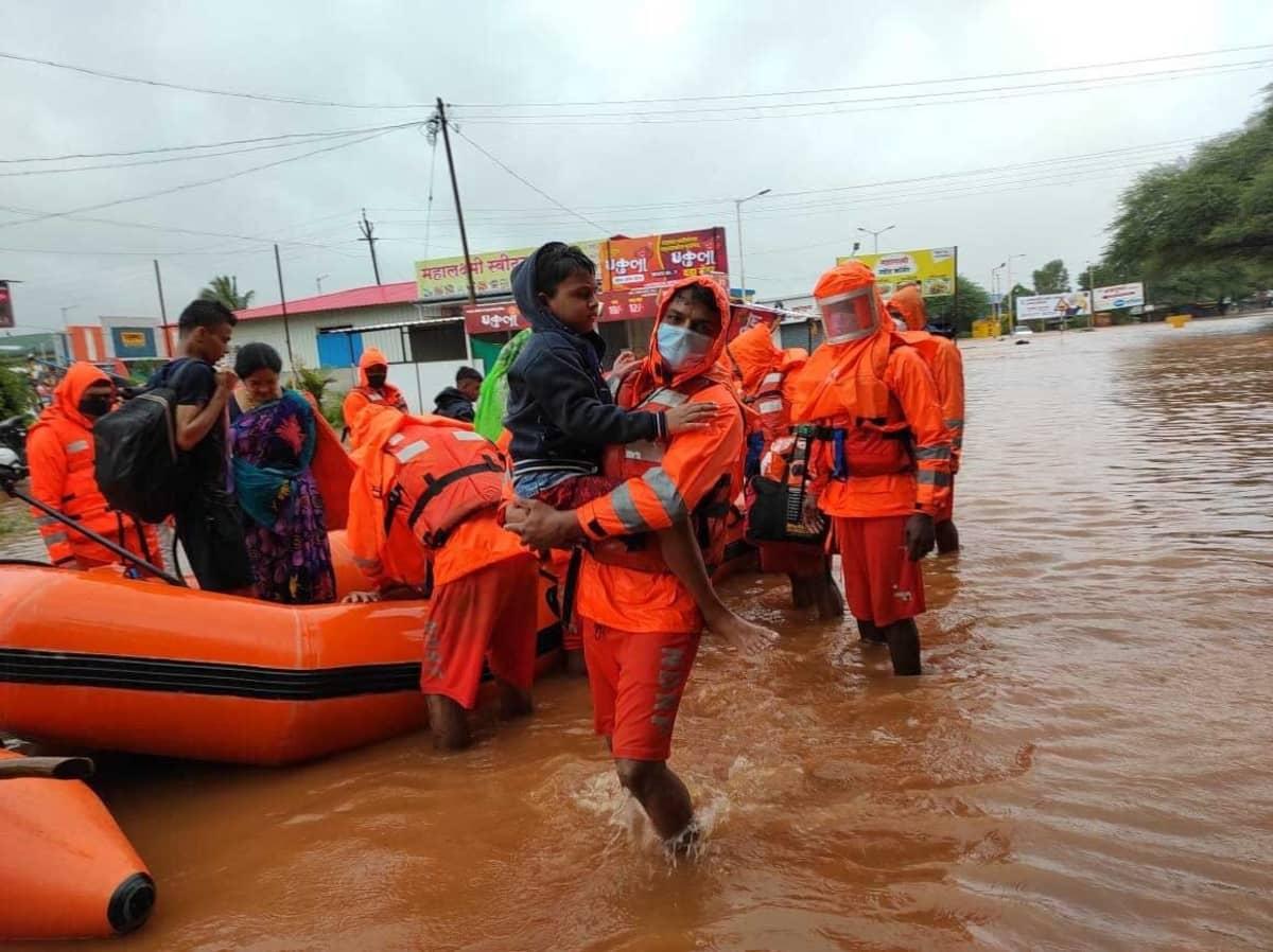 pelastustyöntekijä kantaa lasta tulvavedessä. Vieressä muita pelastustyöntekijöitä ja pelastettuja asukkaita.
