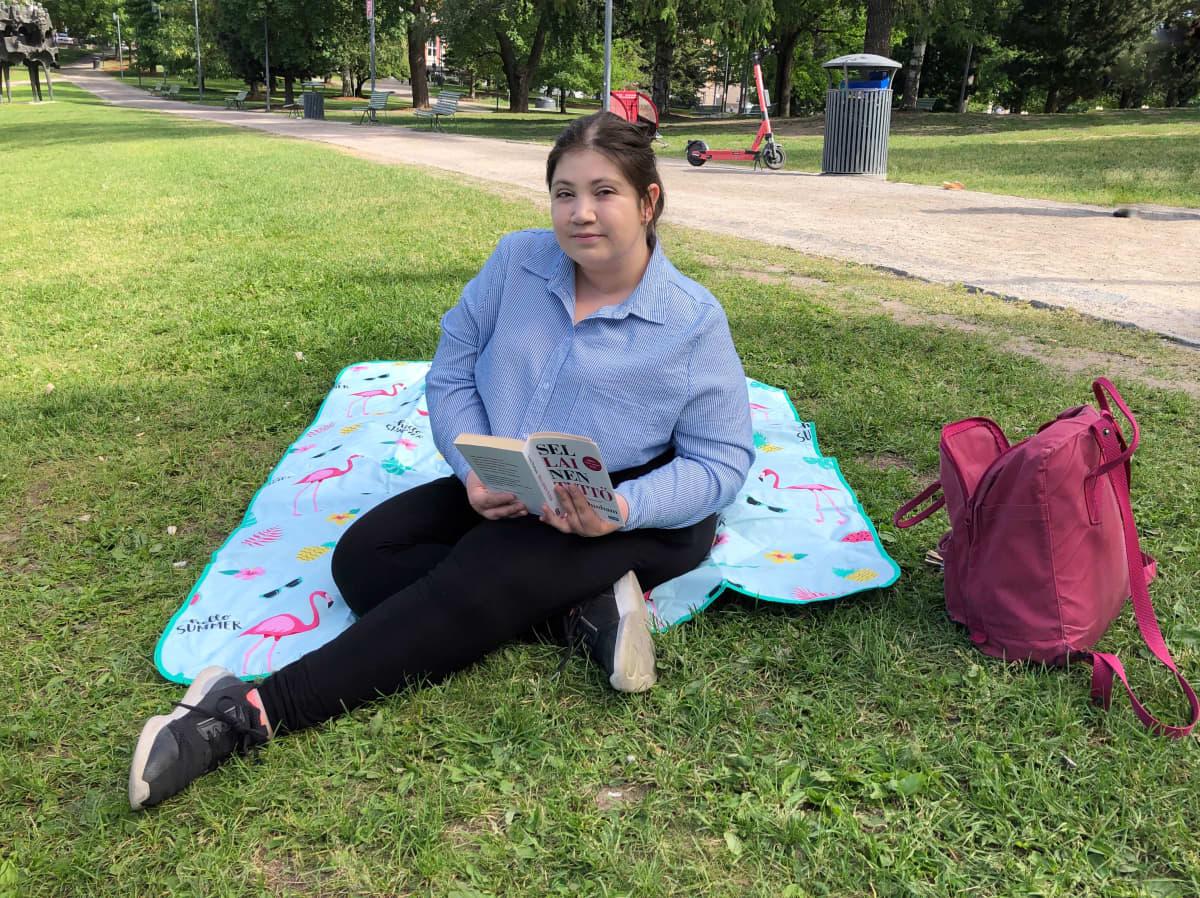 Tummahiuksinen nainen istuu viltillä nurmikolla lukemassa kirjaa.