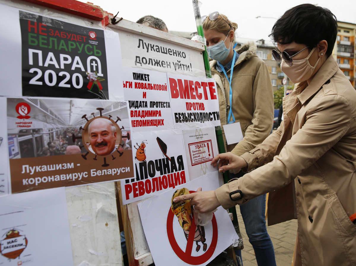 Opposition kannattajat liimaavat julisteita Valko-Venäjällä
