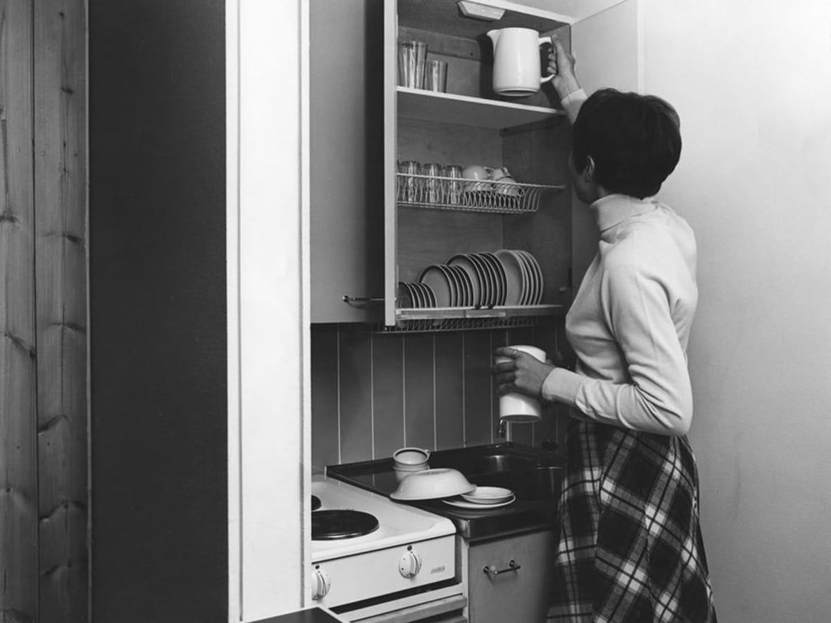 nainen ottaa kannua keittiön kaapista