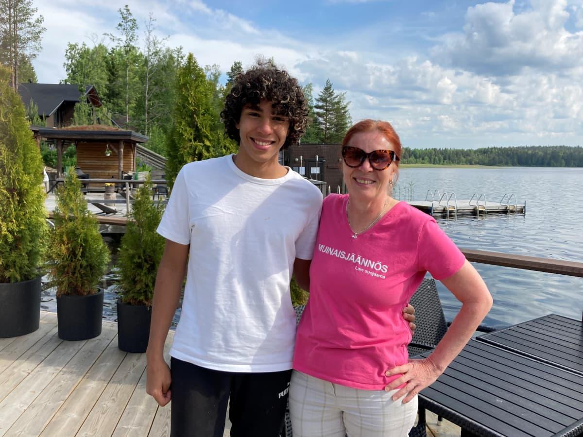 Poika ja hänen äitinsä seisovat terassilla veden äärellä hymyillen.