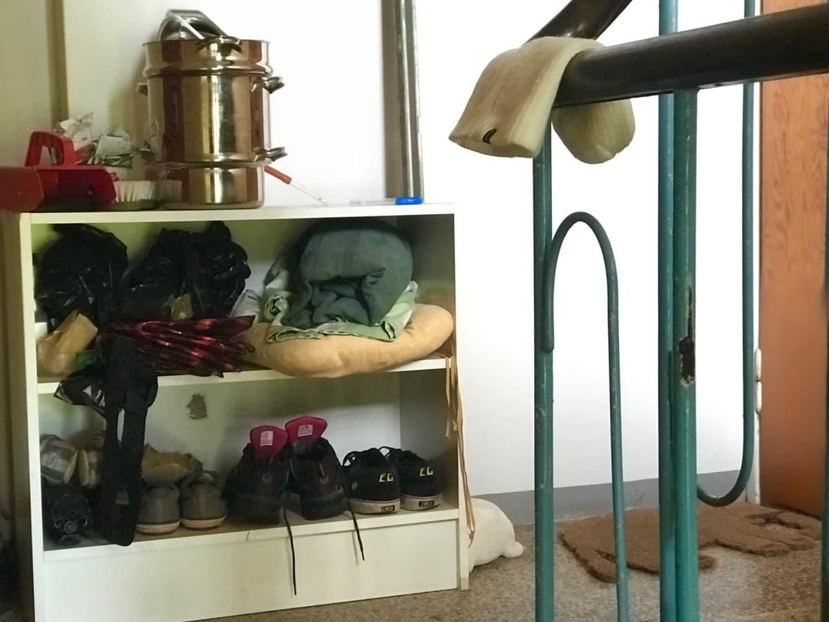 Kenkiä ja mehumaija hyllyllä vanhan kerrostalon rappukäytävässä.