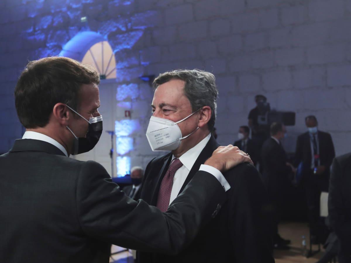 Macron ja Draghi pitävät toisiaan olkapäistä kiinni.