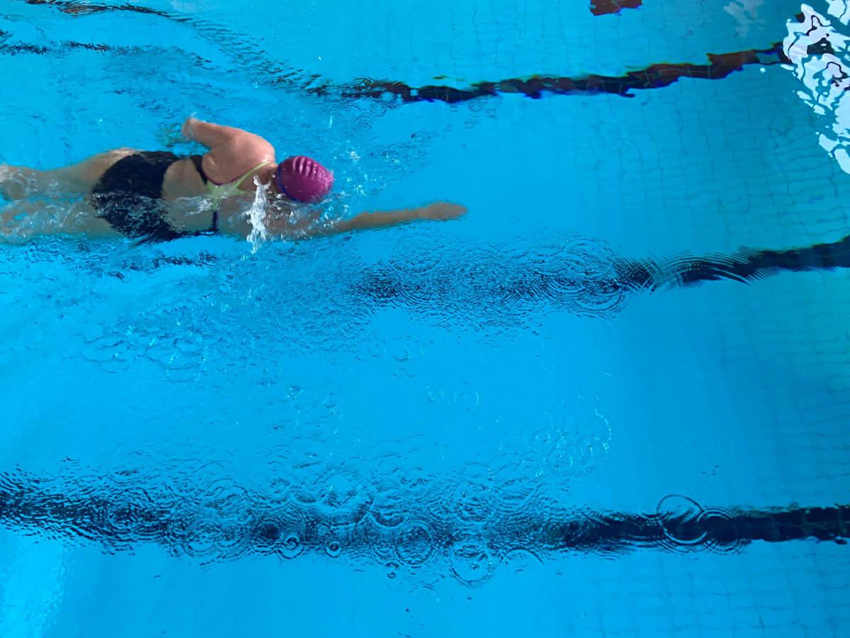 En person simmar i en simbassäng.